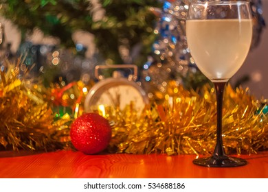 Christmas and New Year celebration holiday with glass of white wine and red ball covered with yellow fir and clock