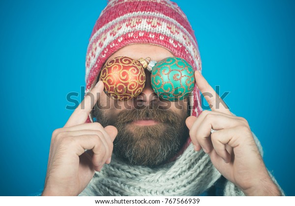 Christmas new year celebration. Holiday decorations and ornaments. Bearded hipster in hat and scarf holds decoration balls instead of eyes. Festival and decor concept.