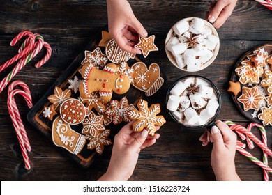 Christmas and New Year celebration traditions. Friends drinking hot chocolate eating freshly baked gingerbread cookies. Female hands with mugs of sweet cocoa. Warming concept, winter holidays