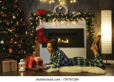 Christmas or New Year celebration. Woman lying beside fireplace.