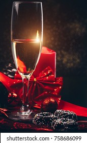 Christmas or New Year. Champagne in glasses with candles, panettone and gift with red satin bow. Copy-space. Holiday Concept
