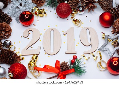 Christmas and New Year composition. 2019 simbols and fir branches with cones and christmas balls in silver and red colours on white background. Flat lay, top view, copy space for text
