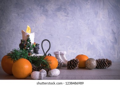 Christmas or New Year composition with a candle, tangerines, and Christmas decorations, pine cones, a place for text. holiday composition of the new year. postcard.