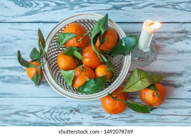 Christmas or New Year composition with a candle and tangerines on a white wooden background.