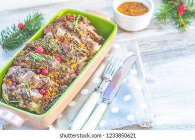 Christmas and New Year composition with delicious baked meat with cranberry and spices, spruce branches, cutlery on light gray surface, copy spice, Holidays background, Christmas table place setting