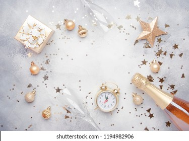 Christmas or New Year composition, frame, gray background with gold Christmas decorations, stars, snowflakes, balls, alarm clock, gift box, glasses and bottle of champagne, top view