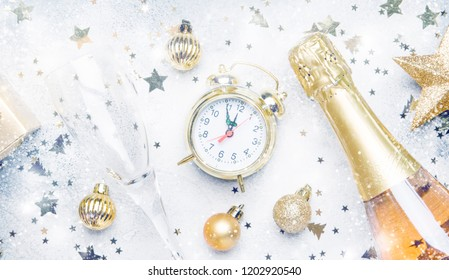 Christmas or New Year composition, frame, gray background with gold Christmas decorations, stars, snowflakes, balls, alarm clock, gift box and bottle of champagne, top view