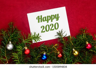 Christmas and New Year composition with numbers 2020 and branches of Christmas tree with balls on red background with top view