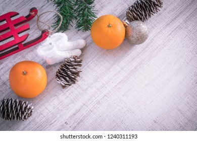 Christmas or New Year composition on a wooden background with red sleds, tangerines and Christmas decorations, pine cones, place for text. holiday composition of the new year. view from above.copy