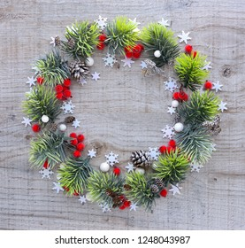 Christmas or new year composition. Round frame made of christmas decorations and spruce branches on wooden background. Holiday and celebration concept for postcard or invitation. Top view