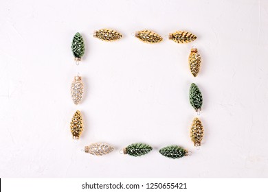 Christmas or New Year composition. Square frame from decorative golden, green and silver pine cones on white textured background. Top view. Flat lay. Place for text.