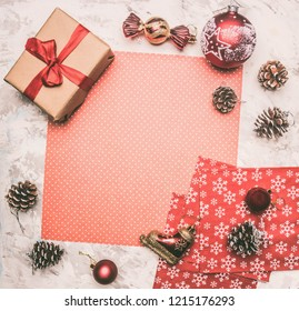 Christmas and New Year concept, Christmas decorations, gifts and cones lined around the red wrapping paper, place for text