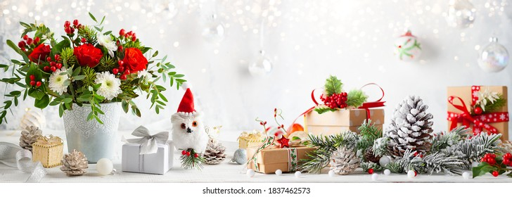 Christmas or New Year concept with flower arrangement, gift boxes and Christmas decorations on table. Festive still life.