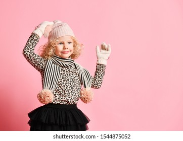 Christmas and New Year concept. Little baby girl with curly blonde hair in scarf with pompon and gloves is touching furry pompon of her warm winter hat on pink with copy space