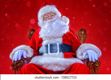 Christmas and New Year concept. Portrait of good old Santa Claus sitting in his armchair. Red background.
