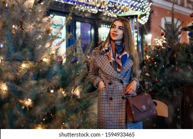 Christmas, New Year concept. Woman walking on city street by decorated trees. Stylish girl enjoying holiday atmosphere