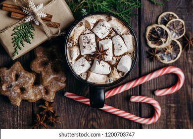 Christmas and New Year cozy holiday composition with gift box, hot chocolate, gingerbread cookies and candy canes. Winter holidays celebration concept