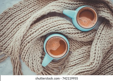 Christmas and New Year cozy holiday composition with cinnamon, scarf, mugs with cocoa or chocolate on the gray concrete background. Flat lay, top view