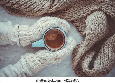 Christmas and New Year cozy holiday composition with scarf, woman hands in mittens, mugs with cocoa or chocolate on the gray concrete background. Flat lay, top view