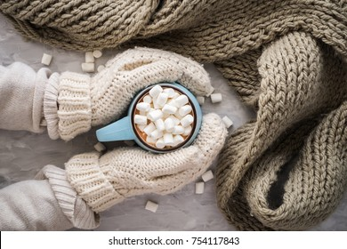 Christmas and New Year cozy holiday composition with scarf, woman hands in mittens, mugs with cocoa or chocolate, marshmallow on the gray concrete background. Flat lay, top view