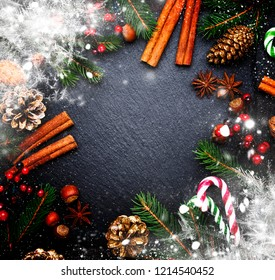 Christmas or New Year dark background, frame, template, with festive decorations, winter spices and Christmas decorations, nuts and fir branches, top view