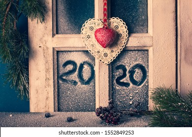 Christmas New Year decor - frame of snow-covered window with hand drawn 2020, fir branches, cones, and two decorative hearts. Cottage interior.