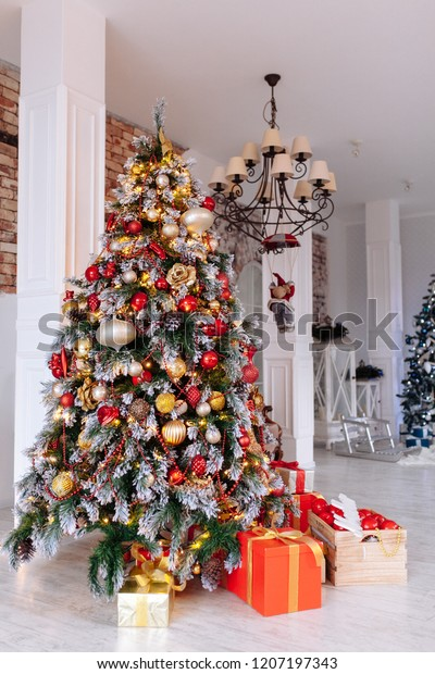 Christmas and New Year decorated interior room with red presents and New year tree in front of white wall.