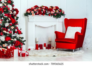 Christmas and New Year decorated white interior room with presents and New year tree. Red textile chair with fireplace