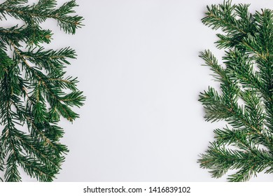 Christmas or New Year decoration background. Fir tree branches on white background with copy space. Top view.