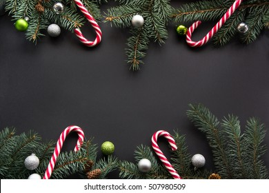 Christmas or New Year decoration background: fir-tree branches, colorful balls, candy cane on black background. Top view with copy space. Falt lay.