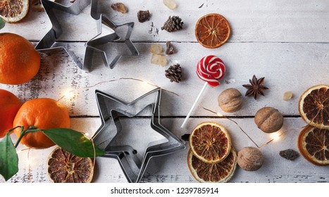 Christmas or New Year decoration, fir tree, tangerine, candy cane, dry oranges, sugar, wallnuts and cookie cutters on white wooden background. Top view