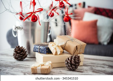 Christmas or new year decoration on modern wooden coffee table. Cozy sofa with pillows on a background. Living room interior and holiday home decor concept