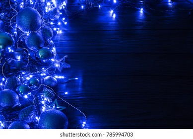 Christmas and New Year decorations, balls, stars, gatlands and fairy lights on a dark background.