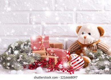 Christmas and New year decorations. Bear toy, wrapped christmas presents, fur tree branches, balls and  red berries on white textured  background. Selective focus. Drawn snow effect.