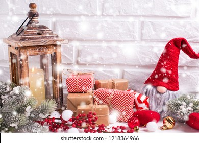 Christmas and New year decorations. Elf, wrapped christmas presents, fur tree branches, balls, candle in lantern and  red berries on white textured  background. Snow effect. Selective focus.