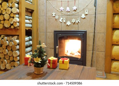 Christmas and New Year decorations at the wood-burning stove in a rural wooden house.
