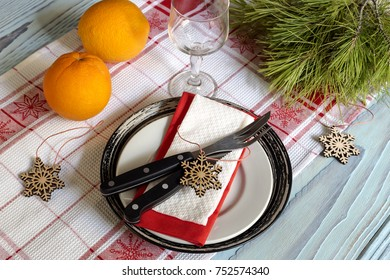 Christmas and New Year design. Plate, knife, fork, glassful, oranges and a variety of Christmas decorations on a table close-up.