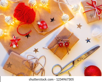 Christmas and New Year DIY presents in craft paper with toy train. Gifts tied with threads with red heart and star symbols. Metal light bulbs with delicate pattern.