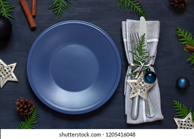 Christmas New Year empty plate flat lay on the dark wooden table. Holiday top view. Copy space