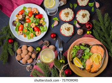 Christmas or New Year Family Dinner Setting Table Concept with Holiday Decoration. Delicious Roast Steak Salmon, Salade, Appetizers and Dessert on Stone Dark Table. Top view