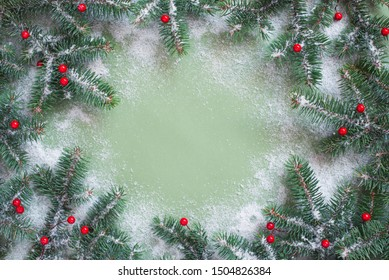 Christmas or New Year festive background with spruce branches and snow on green paper surface, copy space