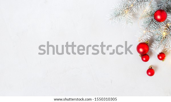 Christmas or New Year festive background with frosty fir branches and red Christmas balls, winter holiday image, copy space