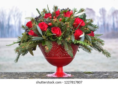 Christmas or New Year floristry centerpiece with red roses and fir tree.