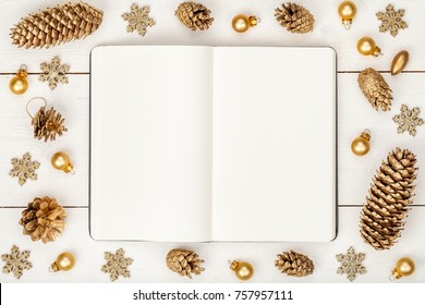christmas or new year frame composition. mockup of book and golden christmas decorations on wooden background. holiday and celebration concept for postcard or invitation. top view