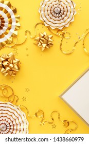 christmas or new year frame decorations and frame in gold colors on yellow  background with copy space for text. Xmas, party,  holiday and celebration concept for postcard or invitation. top view