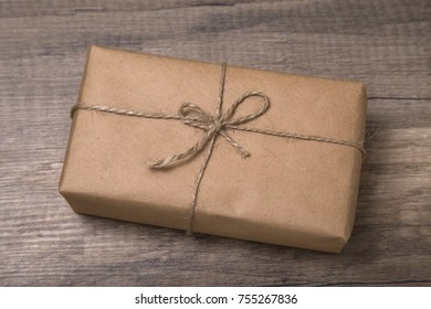 Christmas or New Year gift box wrapped in kraft paper with blank gift tag on old wooden background.