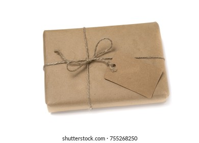 Christmas or New Year gift box wrapped in kraft paper with blank gift tag isolated on white background