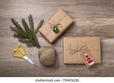 Christmas or New Year gift boxes wrapped in kraft paper with blank gift tag on old wooden background.