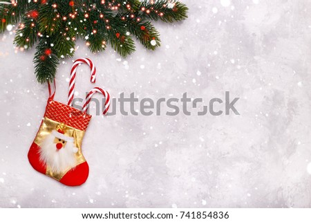 christmas or new year greeting card hanging stocking with candy canes on pine tree branch