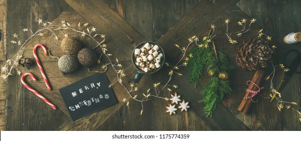 Christmas, New Year holiday background. Flat-lay of greeting card, glittering toys, mug of hot chocolate, cinnamon, scissors, light garland, pine cone over wooden table, top view